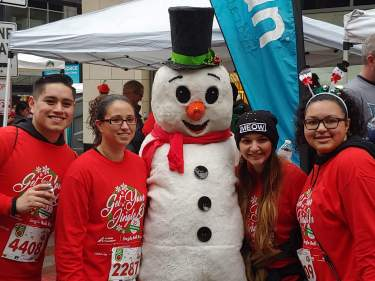 Finishers pose with the snowman after the race